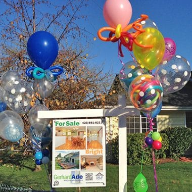 Sign with balloons for open house.